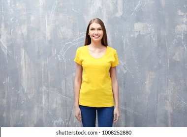 Young woman in color t-shirt on grunge background. Mockup for design