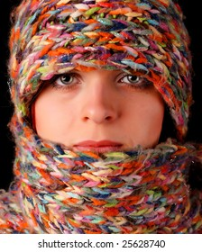 young woman in color wool scarf at black background