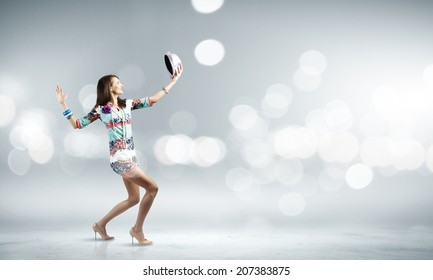Young woman in colored dress and hat dancing against bokeh background