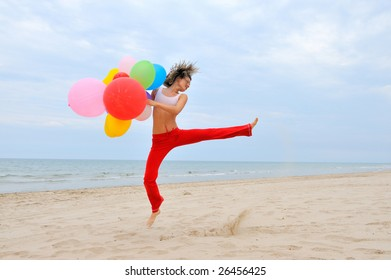 young woman with colorful balloons jumping on the beach