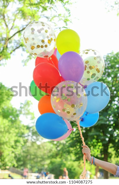 Young woman with colorful balloons outdoors on sunny day
