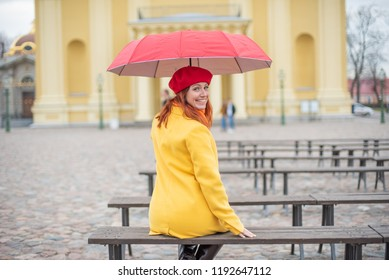 A young woman in colorful body clothes with a red umbrella sits alone on the bench with her back, smiling back. A girl sits on a bench in a yellow coat and an umbrella in the autumn.