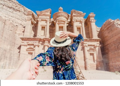 Young woman in colorful dress and hat holding man's hand and leading him to The Monastery, Petra's largest monument, UNESCO World Heritage Site, Jordan.
