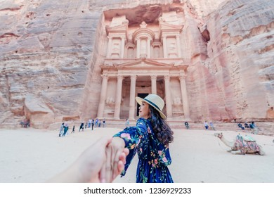 Young woman in colorful dress and hat holding man's hand and leading him to Al Khazneh - the treasury, ancient city of Petra, Jordan. Traveling together. Follow me.