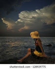 Young woman with colorful dress and hat sits on rocky shore with storm on the horizon.
