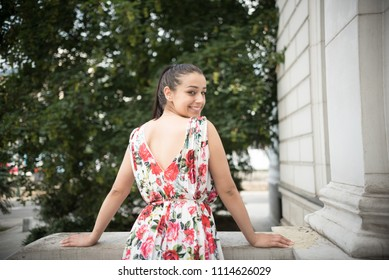 young woman in colorful dress smiling on veranda