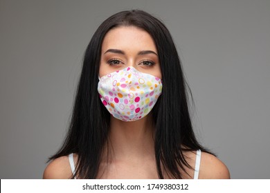 Young woman in a colorful fabric face mask during the coronavirus pandemic in a head and shoulders portrait on grey conceptual of the fashion style