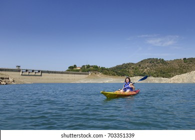 Young woman with a colorful kayak at summer