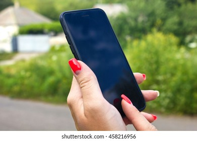 Young woman with colorful nails holding phone in her hand