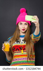 Young woman in colorful winter outfit and knitted hat, posing taking a selfie on smartphone and holding a glass of juice. Black background, studio lighting, no retouch.