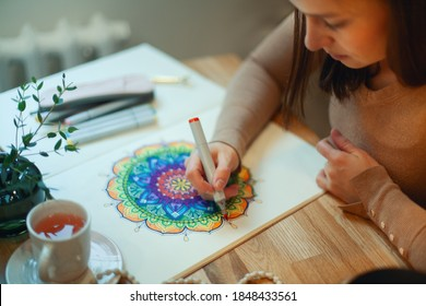 Young woman colouring mandala with markers and white rosary on table with cup of coffee near flower vase at home. Art therapy and meditation concept. Hobby and leisure during quarantine. Wellbeing.
