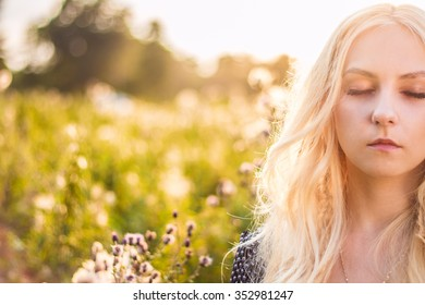Young woman with colsed eyes in a meadow - otdoor image