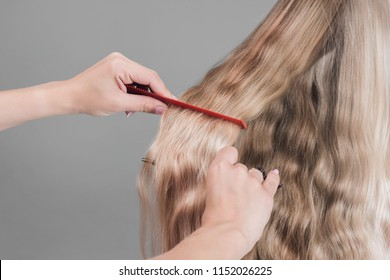 Young woman with comb brushing her wet, blonde, perfect hair on the gray background. Care about beautiful, healthy and clean hair. Beauty salon concept. Side view.