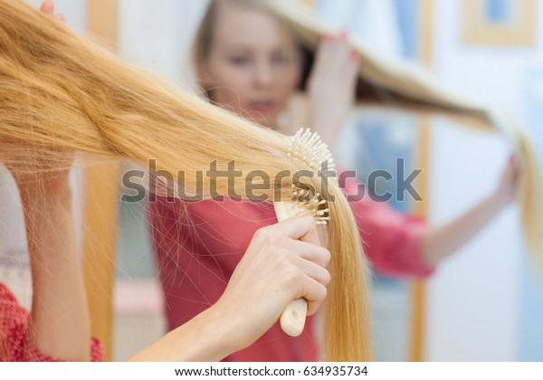 Young woman combing brushing her long blonde smooth hair in bathroom, using brush, looking in mirror. Girl taking care refreshing her hairstyle. Haircare concept.
