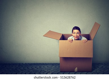 Young woman coming out from a box