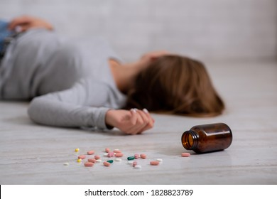 Young woman committing suicide by overdosing on pills, focus on bottle of tablets scattered on floor. Depression and drug overuse, mental breakdown or PTSD problem concept