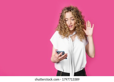 Young woman communicates through the phone by video link, expressing emotions. Female portrait. Isolated on pink background