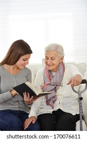 Young woman in community service reading books to senior citizens