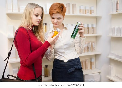 Young woman comparing cosmetics products with saleswoman in a drugstore