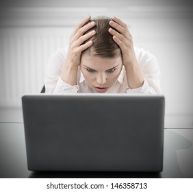 Young woman with computer worried about work done. Portrait of businesswoman with scared expression sitting in the office.