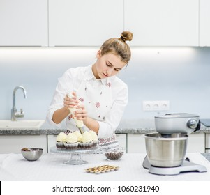 Young woman with confectionery bag squeezing  cream on cupcakes