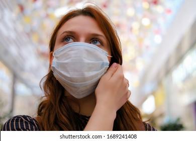 Eine junge Frau erwägt, die medizinische Maske nach dem Ende der Quarantäne aufgrund des Coronavirus zu entfernen. Porträt eines Mädchens nach der Grippeepidemie, Nahaufnahme