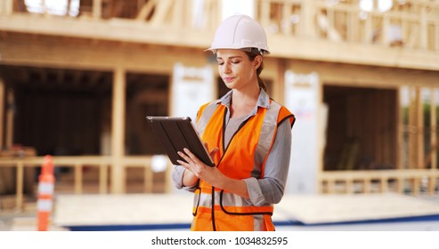 Young woman construction manager directing traffic in front of project