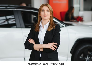 Young woman consultant in show room standing near car