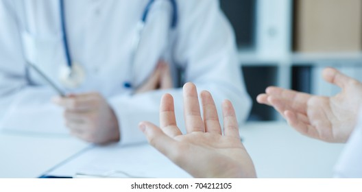 Young woman consulting with medical doctor, complaining about health, having problems. Focus on  patient's hands. Private health care facility reception, admission complaints.