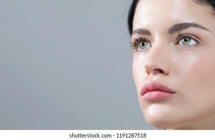 Young woman with contact lenses on a gray background