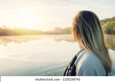 Young woman contemplating nature by the lake at sunrise, springtime, France, Europe. People travel relaxation in nature concept. Tones image