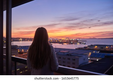 Young woman contemplating the sea from a balcony