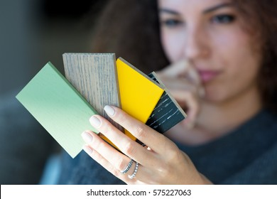 Young woman contemplating wooden color swatches with a thoughtful expression and hand to her mouth, focus to the samples for decorating and renovation