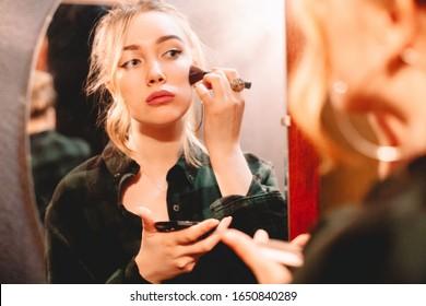 Joven que se contamina la cara con maquillaje y se mira en el espejo en casa preparándose para salir