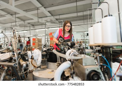 Young woman controlling automated production of textile thread and cotton spinning