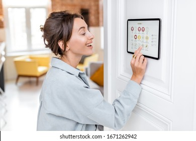 Young woman controlling home with a digital touch screen panel installed on the wall in the living room. Concept of a smart home and mobile application for managing smart devices at home