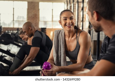 Young woman in conversation with man in gym after workout training. Smiling sweaty girl taking break after workout exercise. Exhausted people talking to each others while sitting on rowing machine.