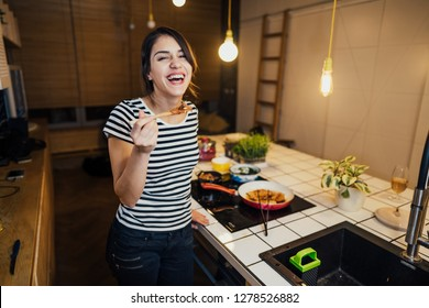 Young woman cooking a healthy meal in home kitchen.Making dinner on kitchen island.Preparing fresh meal,enjoying spice aromas.Eating in.Passion for cooking.Healthy lifestyle and dieting concept.