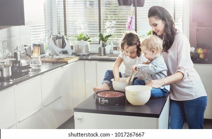Young woman cooking with her babies, at home