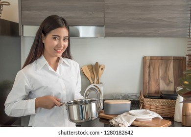 Young woman cooking in her kitchen standing near stove and holding pot .