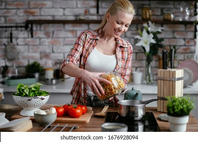Young woman cooking in kitchen. Beautiful woman making delicious food.