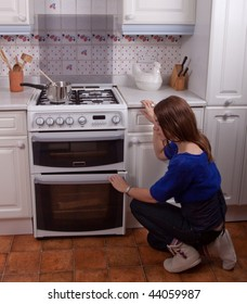 Young woman cooking in the kitchen opening the oven door