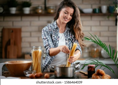 Young Woman Cooking in the kitchen.  Woman cooking pasta dish.