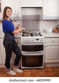 Young woman cooking in the kitchen stirring the saucepan