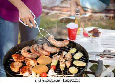 Young woman cooking meat and vegetables on barbecue grill outdoors