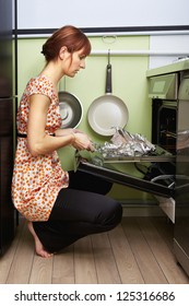 young woman cooking in oven at kitchen