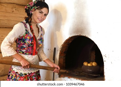 Young woman cooking in a typical Russian stove