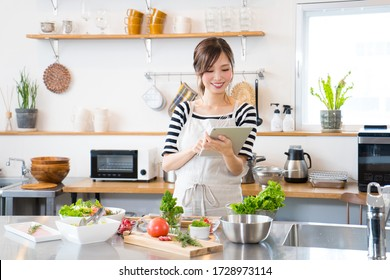 Young woman cooking while looking at a tablet