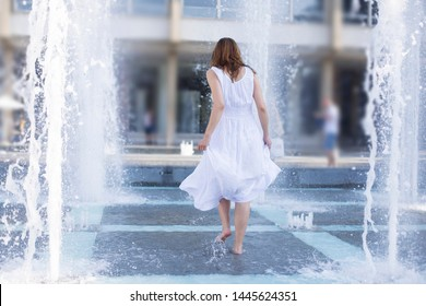 young woman cooling down in fountain water spray during summer heat