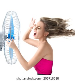 Young woman cooling face under wind of cooler fan isolated on white background